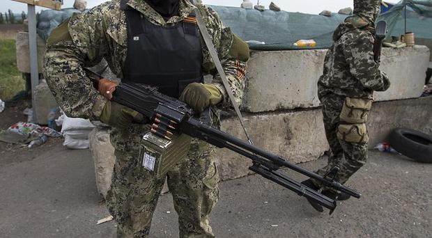 Pro-Russian armed militants guard a checkpoint blocking the major highway at Kharkiv, outside Slovyansk, as Ukrainians prepare to vote in the presidential election (AP Photo/Alexander Zemlianichenko)