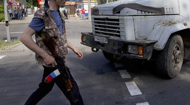 A Pro-Russian militia man walks at a checkpoint on a road leading to the airport in Donetsk (AP)