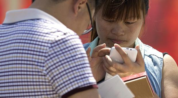 Chinese people use their smartphone on Tiananmen Square in Beijing, as the the government targets instant messaging services (AP)
