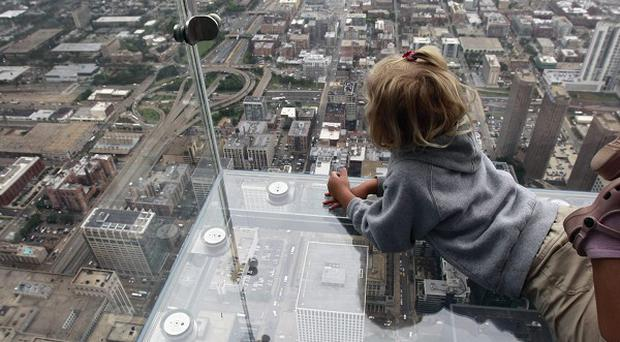 Tourists can stand on The Ledge at Chicago's Willis Tower and see the city below (AP)