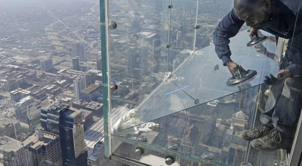 Glaziers replace a layer of protective coating over the glass surface on the floor of a transparent ledge that juts out from Chicago's Willis Tower (AP Photo/M. Spencer Green)