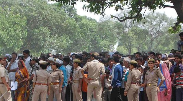 Indian policemen cordon off the area as villagers and others look towards the tree where two teenage girls were found hanging after they were gang raped (AP)