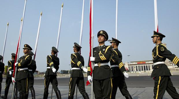 People's Liberation Army soldiers holding red flags march to their positions outside the Great Hall of the People near Tiananmen Square (AP)