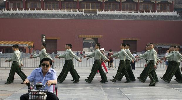Paramilitary police march in front of the entrance to the Forbidden City near Tiananmen Square (AP)