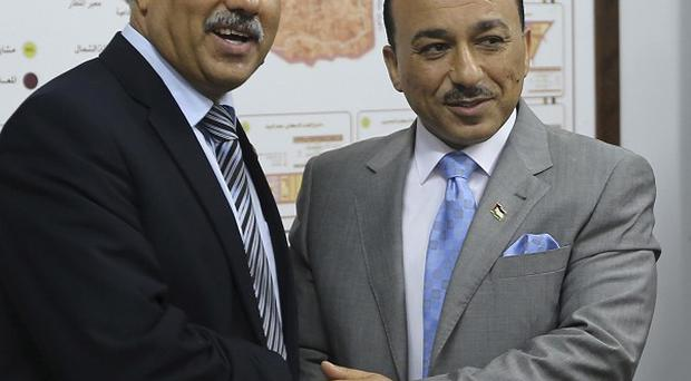 Outgoing Hamas housing minister Yousef Jhariz, left, shakes hands with Mofeed Hassayna, right, the new minister in the Palestinian unity government, which has angered the Israeli government (AP)