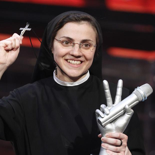 Sister Cristina Scuccia poses with the trophy and a crucifix after winning the final of the Italian version of the TV talent show The Voice in Milan (AP)