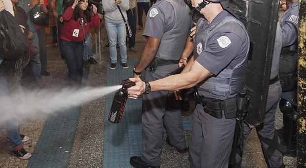 A police officer pepper sprays strikers and protesters during a clash with riot police in front of the Ana Rosa metro station in Sao Paulo (AP)