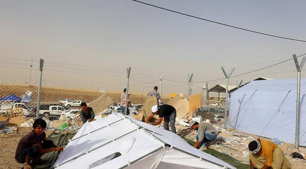 Iraqi refugees from Mosul set up a tent at Khazir refugee camp