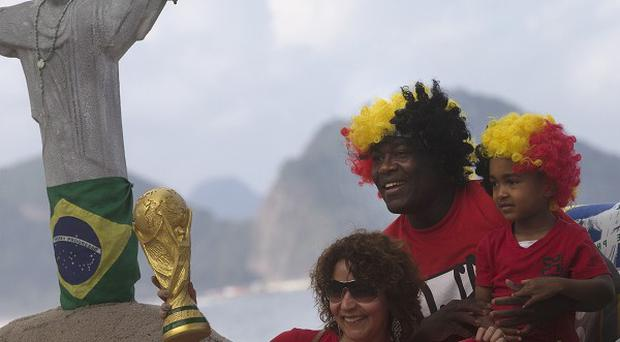 Fans from Belgium pose for a photo with a replica of a World Cup trophy on Copacabana beach in Rio (AP)