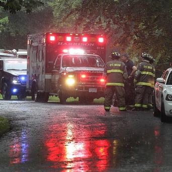Emergency vehicles and personnel stand near a command post set up for a small plane that crashed on a road just west of Westchester County Airport (AP)