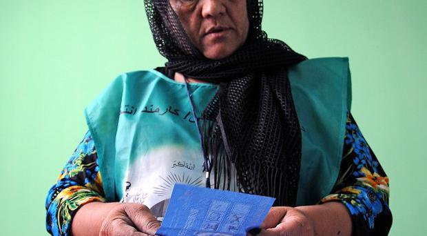 An Independent Election Commission employee counts the ballots at a polling station in Mazar-i-Sharif, Afghanistan (AP)
