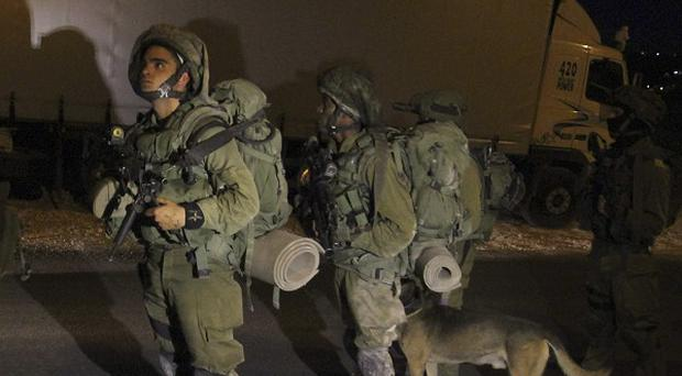 Israeli soldiers patrol during a military operation to search for three missing teenagers near the West Bank city of Hebron (AP)