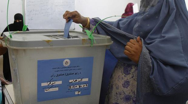 An Afghan woman casts her vote at a polling station in Kandahar, south of Kabul (AP)