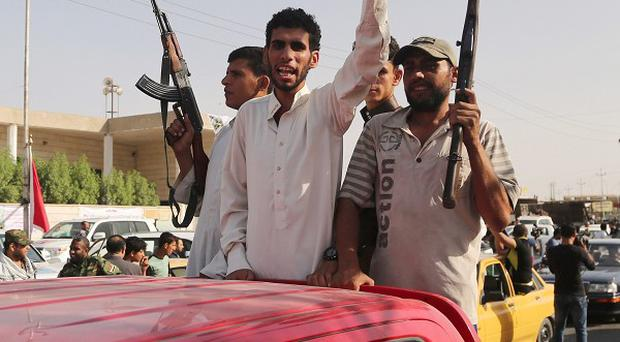 Iraqi Shia fighters deploy with their weapons in Basra, Iraq's second-largest city (AP)