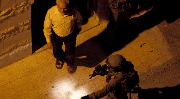 Israeli soldiers arrest Abdel Aziz Dweik, speaker of the long-defunct Palestinian parliament and a senior Hamas figure, during the search for three missing Israeli teenagers (AP Photo/Majdi Mohammed)
