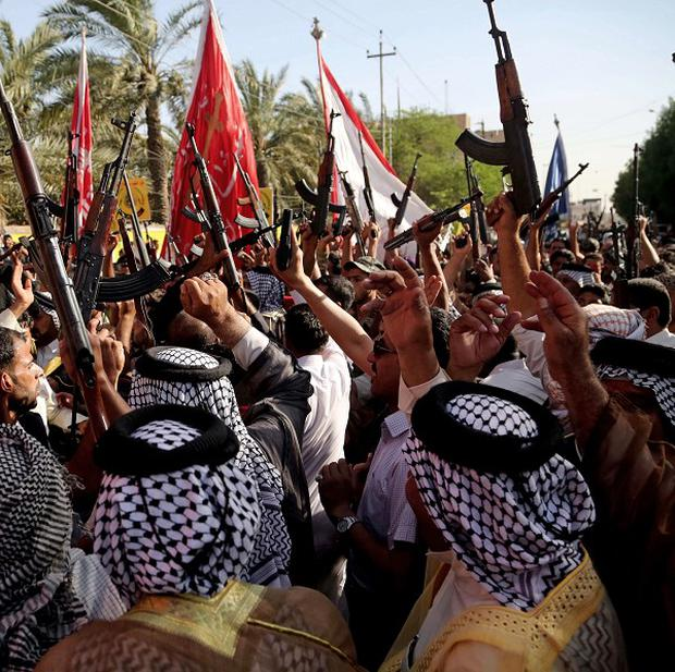 Shiite tribal fighters raise their weapons and chant slogans against the Islamic State of Iraq and the Levant (AP)