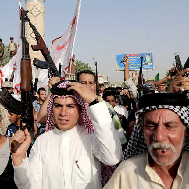 Shiite tribal fighters in Baghdad's Sadr city chant against Isis militants (AP)