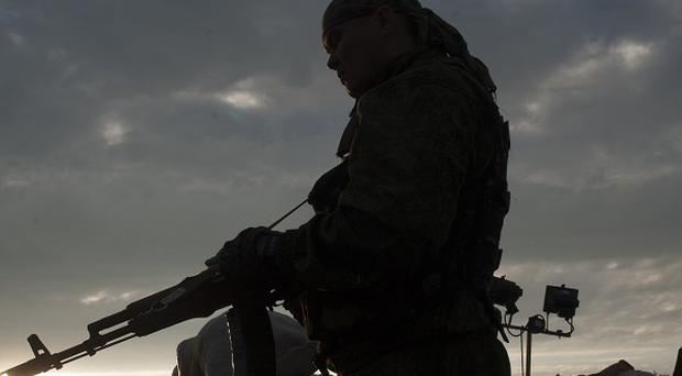 Pro-Russian fighters stand guard at a check point in the village of Karlivka near Donetsk, eastern Ukraine