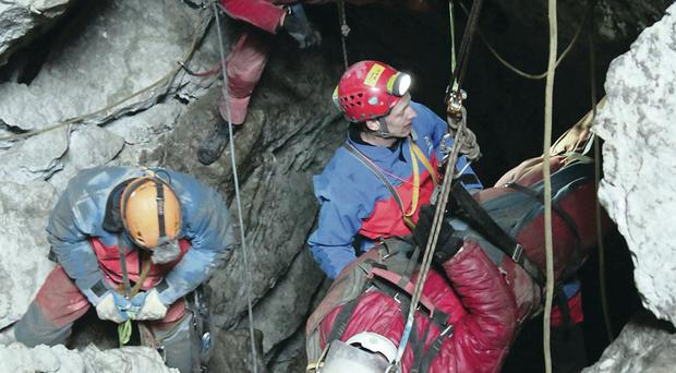Rescue workers bring Johann Westhauser to the surface and carry him to a waiting helicopter whereupon he was transported to hospital