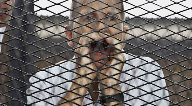 Peter Greste in a cage during his trial on terror charges in Cairo (AP)
