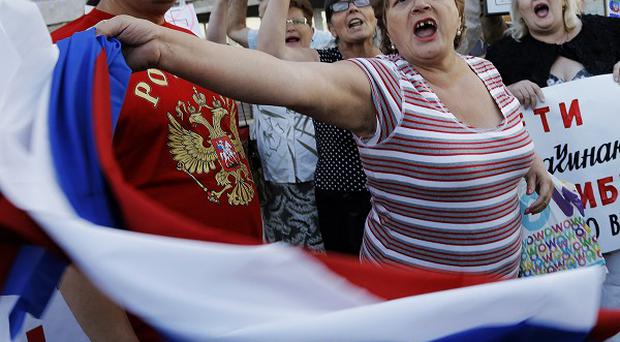 Pro-Russian demonstrators in Donetsk, as insurgents promised to honour a cease-fire declared by the Ukrainian president (AP)