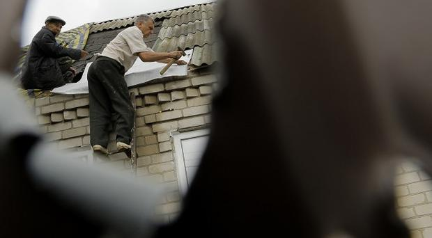 People repair a roof of their home after it was destroyed by a mortar attack from Ukrainian government forces in Slovyansk, Donetsk region (AP)