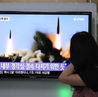 People in Seoul watch a TV news programme showing the missile launch conducted by North Korea (AP)