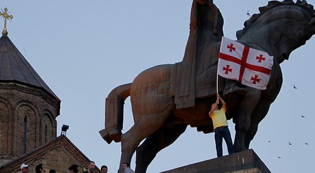 A Georgian man waves a national flag in Tbilisi to mark the signing of the EU agreement (AP)