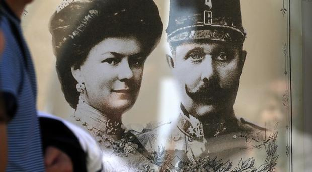 A couple walk past a poster of Archduke Franz Ferdinand and his wife Sophie, in the Bosnian town of Visegrad (AP)