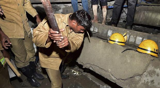 Indian rescue workers search for survivors in the rubble of a collapsed building on the outskirts of Chennai (AP)