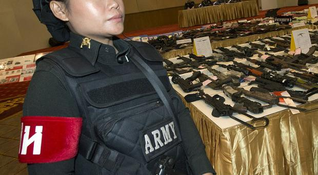 A Thai military police officer with weapons seized during recent raids, as attacks continue in the south (AP)