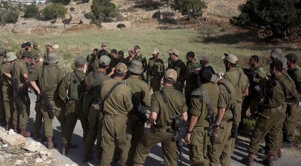 Israeli soldiers receive instructions at the start of a search for three missing Israeli teens feared abducted in the West Bank on June 12 (AP)
