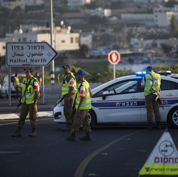 Israeli police block a road near the West Bank town of Hebron, where the bodies of three missing teenagers were found (AP/Majdi Mohammed)