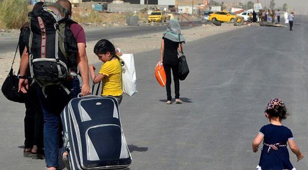 An Iraqi family leave their hometown Mosul, walking towards Irbil, on the outskirts of the city