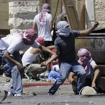 Palestinians throw stones during clashes with Israeli border police in Jerusalem (AP/Mahmoud Illean)