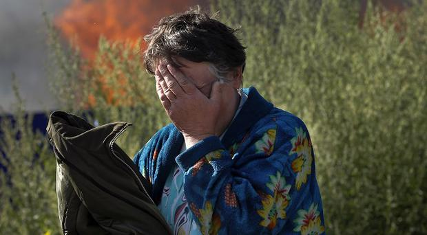 A woman cries near her burning house after shelling in the city of Slovyansk