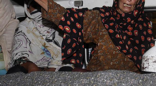 A family member wails over the body of Farzana Parveen in an ambulance in Lahore