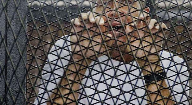 Al Jazeera's award-winning Australian correspondent Peter Greste appears in a defendants' cage in a courthouse near Tora prison in Cairo, Egypt (AP)