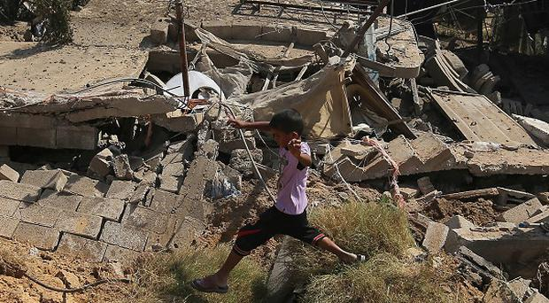Palestinians inspect the rubble of a house after it was hit by an Israeli missile strike in Gaza