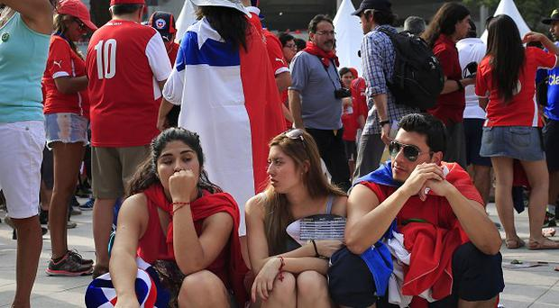 Chile football fans wait for touts with a sign written in Spanish that reads 'We buy tickets for Chile/Spain' (AP)