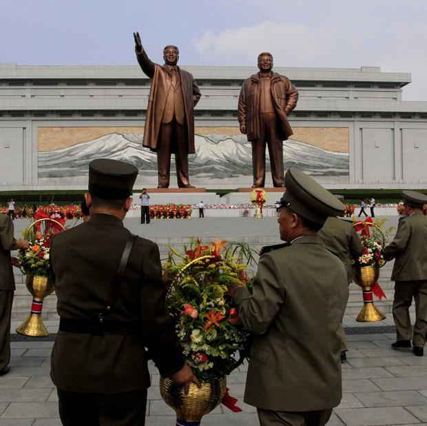 North Korean soldiers bring flowers to the statues of the late leaders Kim Il Sung, left, and Kim Jong Il in Pyongyang (AP)