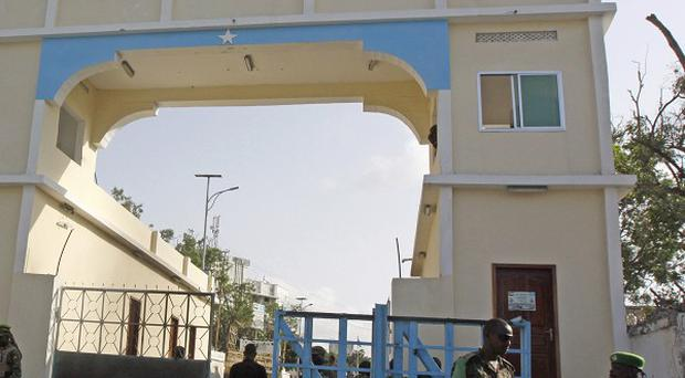 Somali soldiers stand guard at the main gate of the presidential palace in Mogadishu after retaking it from militants (AP)