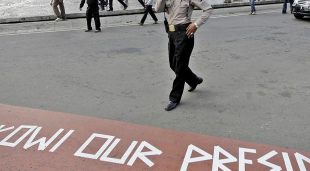 A police officer walks past a message taped on the road by supporters of presidential candidate Joko Widodo (AP)