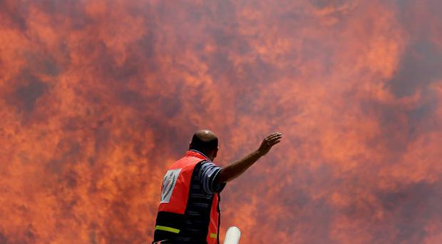 Palestinian firefighters try to extinguish a cargo terminal fire at Karni Crossing between Israel and Gaza (AP/Hatem Moussa)