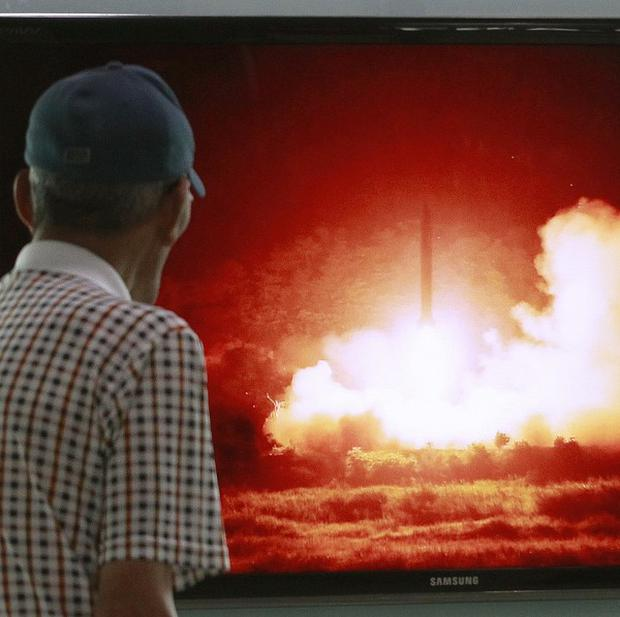 A man at Seoul railway station watches a TV programme showing a file picture of a North Korean missile launch (AP)