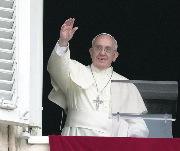 Pope Francis waves to the faithful yesterday from his studio window at St Peter's Square