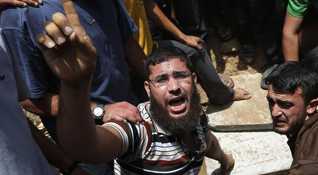 A Palestinian mourner chants slogans on the grave of a member of a family who were killed in an Israeli airstrike (AP)