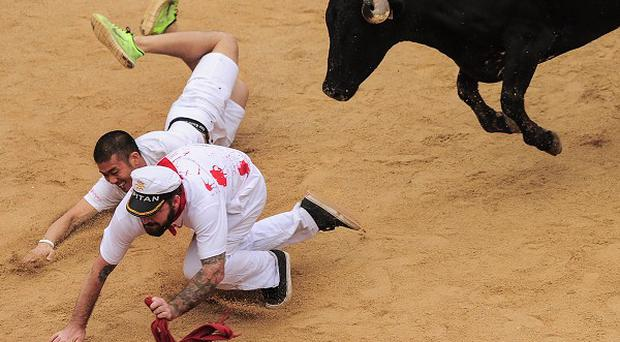 Two revellers fall in the bull ring at the San Fermin festival in Pamplona (AP)
