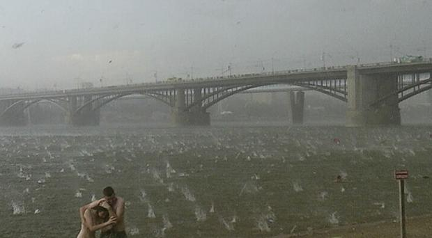 In this photo taken on a smartphone, people run to shelter from hailstorm on the beach at Ob River, the major river in western Siberia in Novosibirsk, Russia (AP)