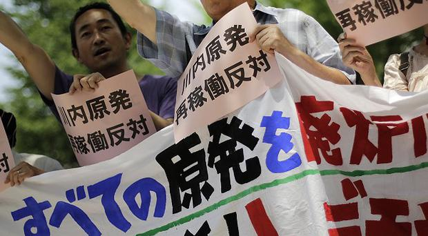 Protesters shout slogans against a Japanese nuclear plant which won preliminary approval for meeting stringent post-Fukushima safety requirements (AP)